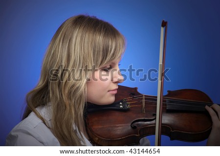 Young female violinist playing on the old violin - stock photo