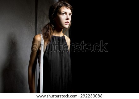 Young female walking lost and alone in a dark scary street alley.  She is suspicious someone is following her from the shadows. - stock photo
