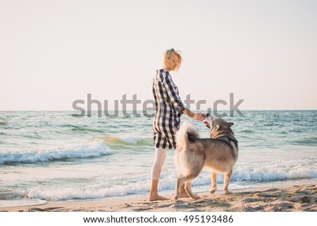 Young female walking with siberian husky dog on sea front at sunrise