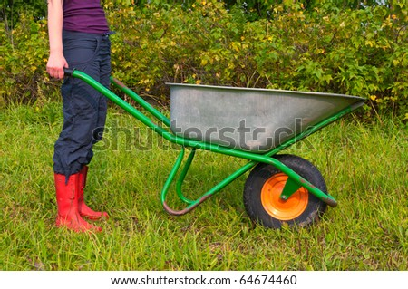 Young female with a wheelbarrow working in a backyard