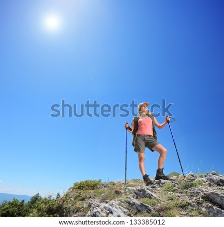 Young female with backpack and hiking poles posing at sunny day in mountain - stock photo