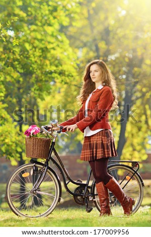 Young female with bicycle relaxing in a park on sunny day - stock photo