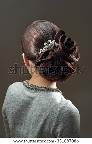 Young female with elegant evening hairstyle posing back to the camera - stock photo