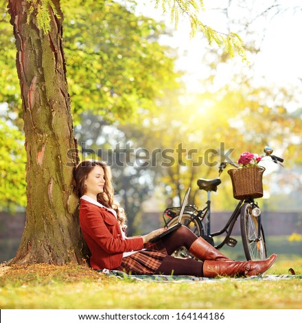 Young female working on a laptop seated on a green grass in a park on a sunny day, shot with a tilt and shift lens - stock photo