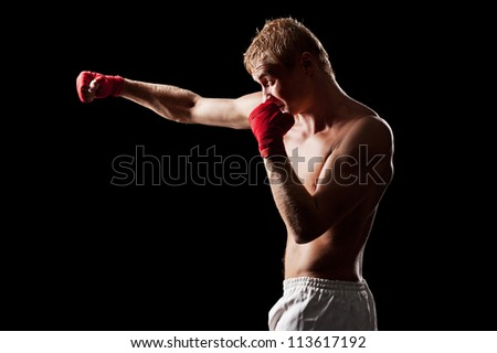 young fighter boxing over black background