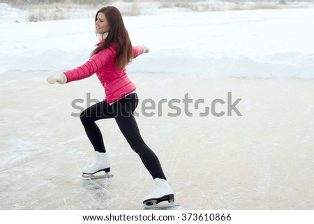 young Figure skating woman at the frozen lake in the winter - stock photo