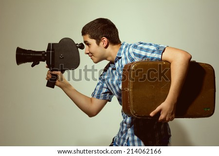 Young filmmaker with old movie camera and a suitcase in his hand. toned photo - stock photo