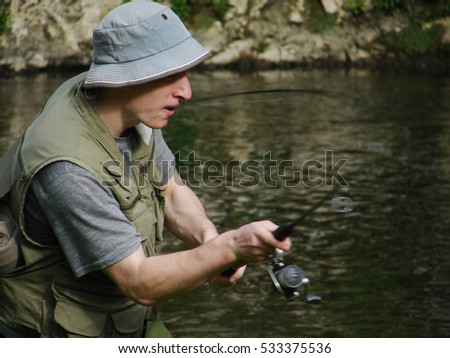 Young fisherman angling on river