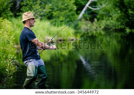 Young Fisherman Catching a big Fish into a Freshwater creek - stock photo