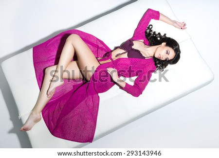 Young, fit, beautiful and sexy woman in a swimsuit. Fashion model posing on a bed. - stock photo