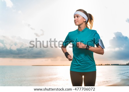 Young fit cute sporty girl in sportswear and band head running on beach at sunset in morning. Fitness, workout and healthy lifestyle concept. Blue sky with clouds and sea on background