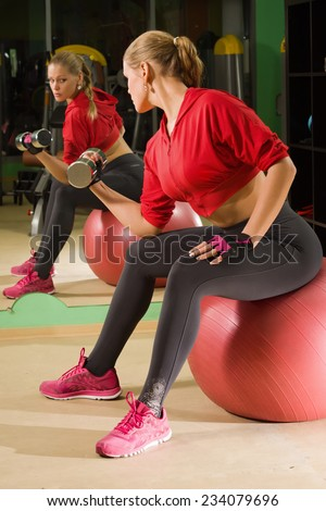 Young fit girl doing exercises with dumbells and looking at her reflection at gym - stock photo