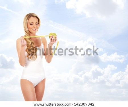 Young fit, healthy and sporty woman over the sky background - stock photo