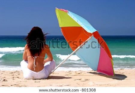 Young, fit, healthy woman sitting under colorful parasol on white sandy beach looking out to sea on a sunny day on vacation.