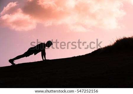 Young fit male doing push ups outdoors.
