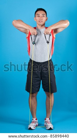 Young fit man with exercise stretch band - stock photo