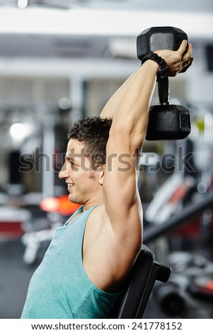 Young fit man working out his triceps and shoulders with a dumbbell in a gym - stock photo