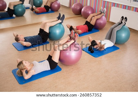 Young fit people doing crunches with fitness ball - stock photo