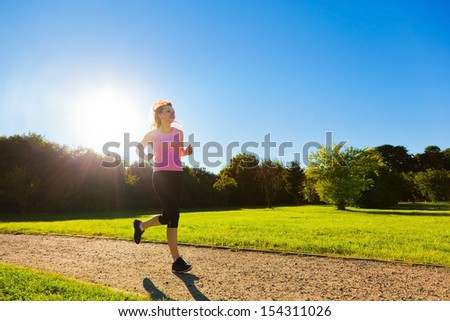 Young fit woman does running, jogging training in a park at summer sunny day - stock photo