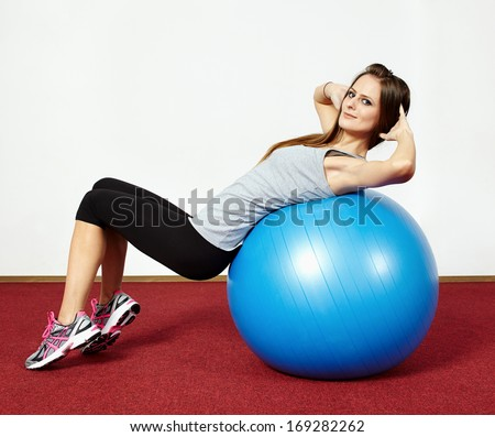 Young fit woman doing abs crunches on a gym ball - stock photo