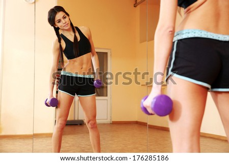 Young fit woman doing exercises with dumbells and looking at her reflection at gym - stock photo