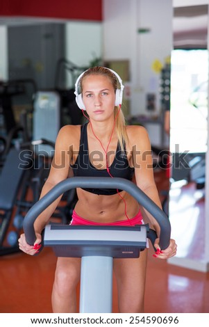 young fit woman doing sport spinning with headset in the gym - stock photo