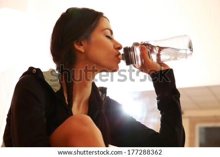Young fit woman drinking water at gym - stock photo