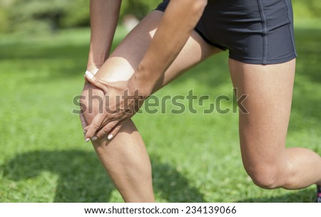 young fit woman has an injury and holding her knee. Arthritis problem at knee. Sports injury concept. - stock photo