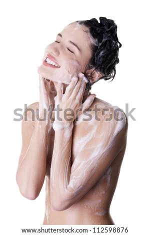 Young fit woman in shower washing her body - stock photo