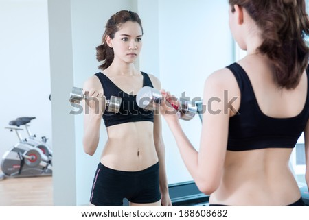 young fit woman lifting dumbbells - stock photo