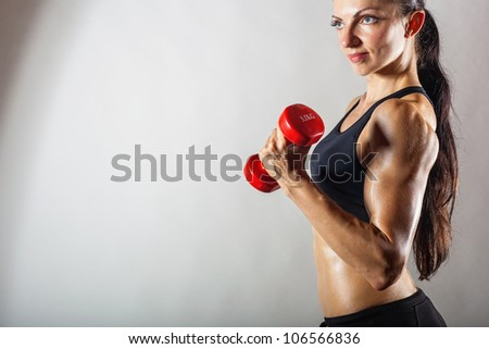 Young fit woman lifting dumbbells on light background. Side view - stock photo