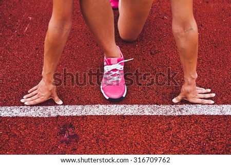 Young fit woman runner athlete at start position in steady pose close to white starting line on stadium with muscled stressed hands and leg at the line preparing to run. Unrecognizable no face photo - stock photo