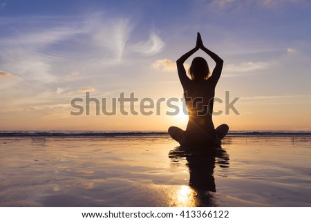 Young fit woman using yoga technique for meditation and well-being on beach at sunrise