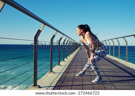 Young fit woman with beautiful figure stretching her legs out before a workout outdoors, female runner warming up before her daily exercise routine on the beach,enjoying nature during fitness training - stock photo