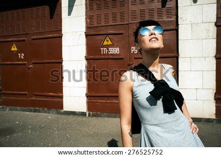 young fit woman with modern haircut in backyard. she is in the direct sunlight. she wears dress and mirrored sunglasses. She has tattoos throughout her body.  - stock photo