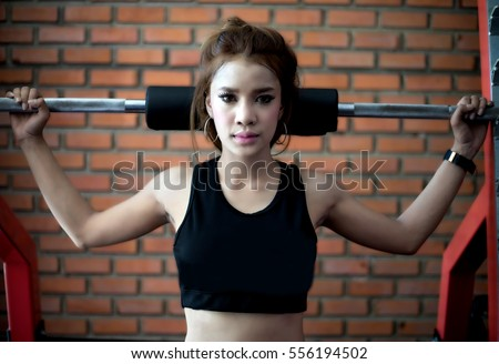 stock photo young fitness asian woman exercise with machine cable crossover and lifting dumbbells and barbells 556194502