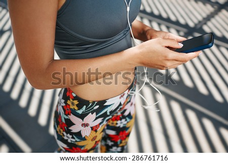 Young fitness blonde woman in sportswear listening music with headphones after training outdoors at beautiful sunny day. Girl runner enjoying the sun and listen music in earphones from smartphone.   - stock photo