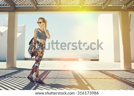 Young fitness blonde woman in sportswear listening music with headphones after training outdoors at beautiful sunny day. Girl runner enjoying sun and listen music in earphones from smartphone. - stock photo