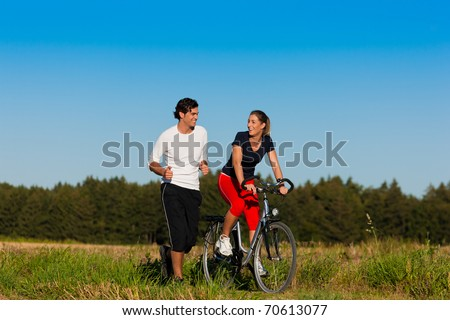 Young fitness couple doing sport outdoors, jogging and riding a bicycle in autumn under a clear blue sky - stock photo