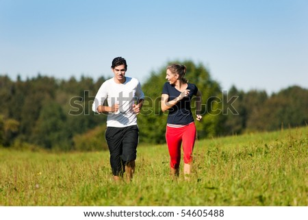 Young fitness couple doing sport outdoors, jogging on a green summer meadow in the grass under a clear blue sky