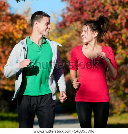Young fitness couple of man and woman jogging in park  - stock photo
