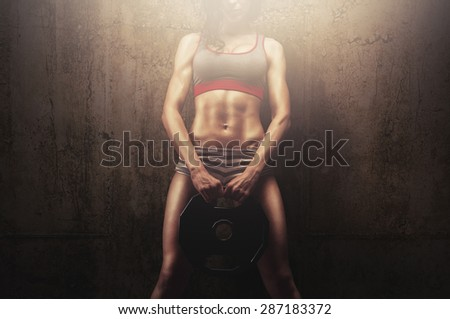 Young fitness female athlete holding weight plate for handles and showing her fantastic muscular body full of strength and tension - stock photo