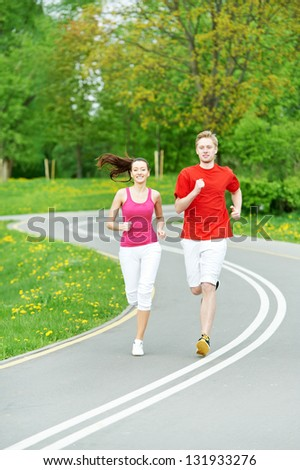 Young fitness man and woman doing jogging sport outdoors - stock photo