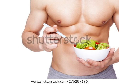 Young fitness man holding a bowl of salad, isolated on white background - stock photo