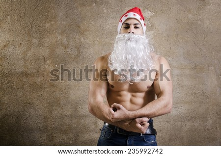 Young Fitness Santa posing on dark Background - stock photo