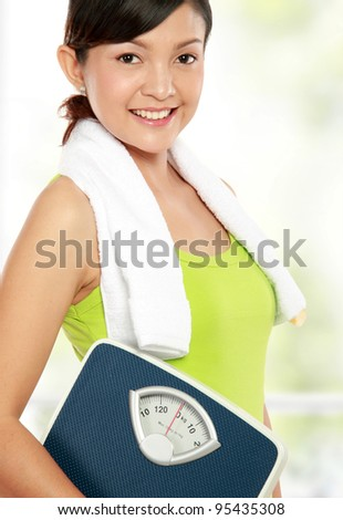 Young fitness woman carrying a weight scale - stock photo