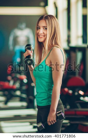 Young fitness woman doing biceps workout with dumbbells, in a gym