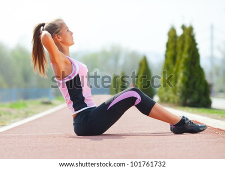 Young fitness woman doing exercises outdoor.