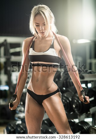 young fitness woman execute exercise with expander in gym, vertical photo - stock photo