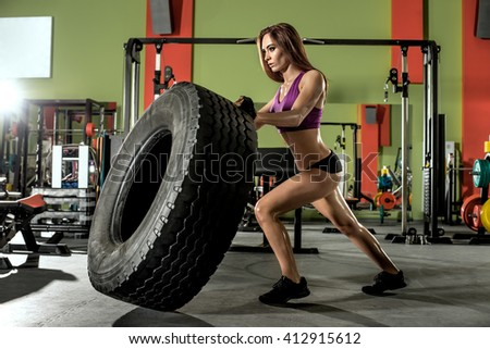 young fitness woman execute exercise with large tire casing, in gym, horizontal photo - stock photo